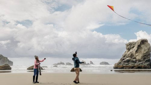 A couple flies kites in front of the iconic Bandon rocks.