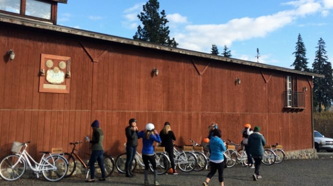 Cyclists get ready for wine-bike tour in front of red barn.