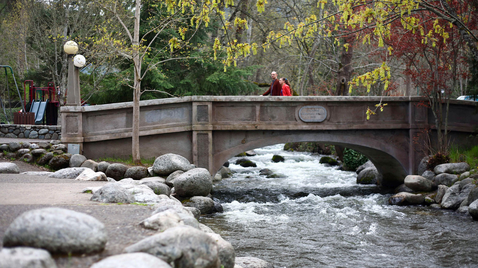 People walk on a bridge over a river during fall.