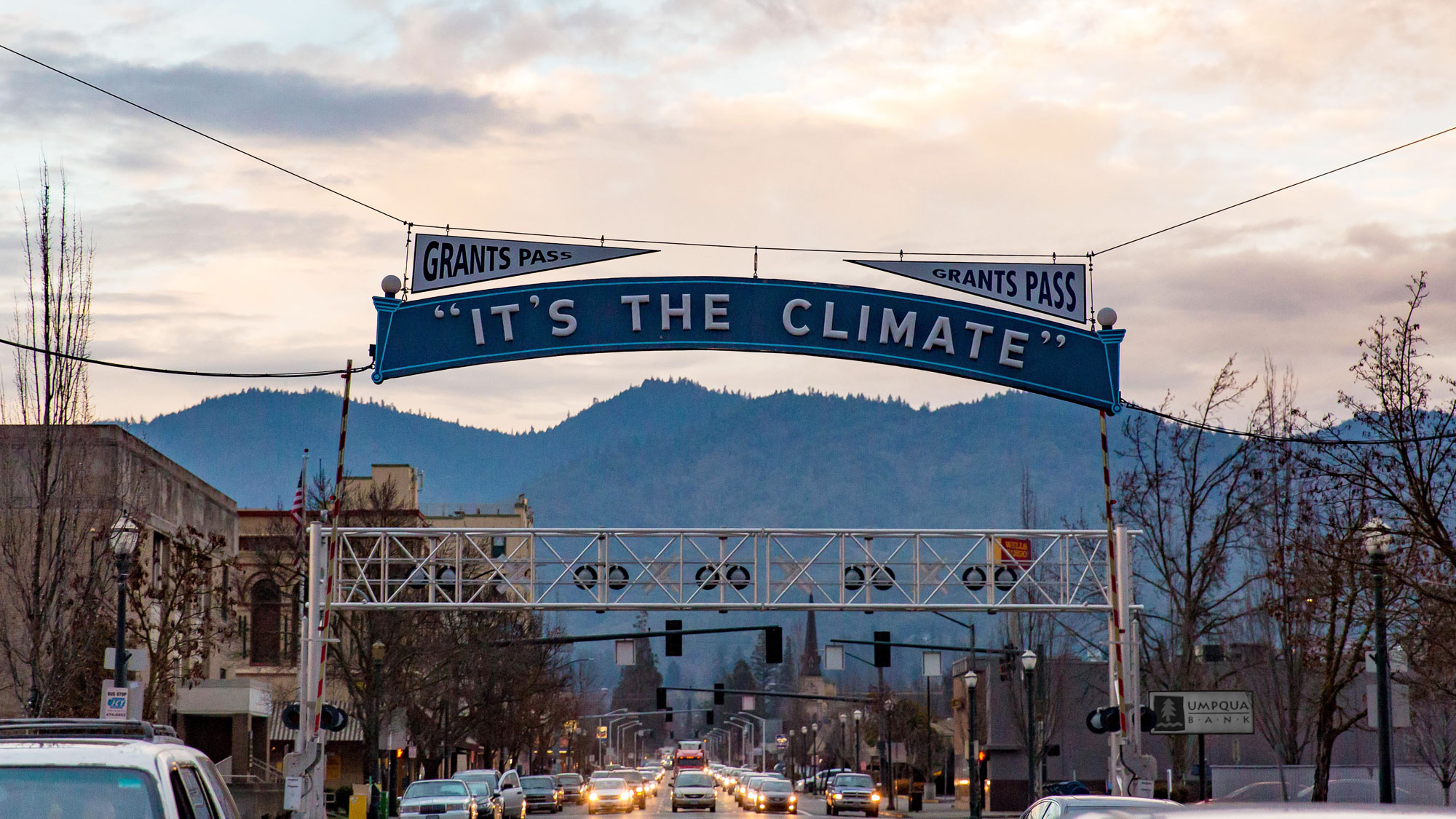 "A pink sunset illuminated a sign reading ""It's the Climate"" that hangs by wire over downtown Grants Pass."