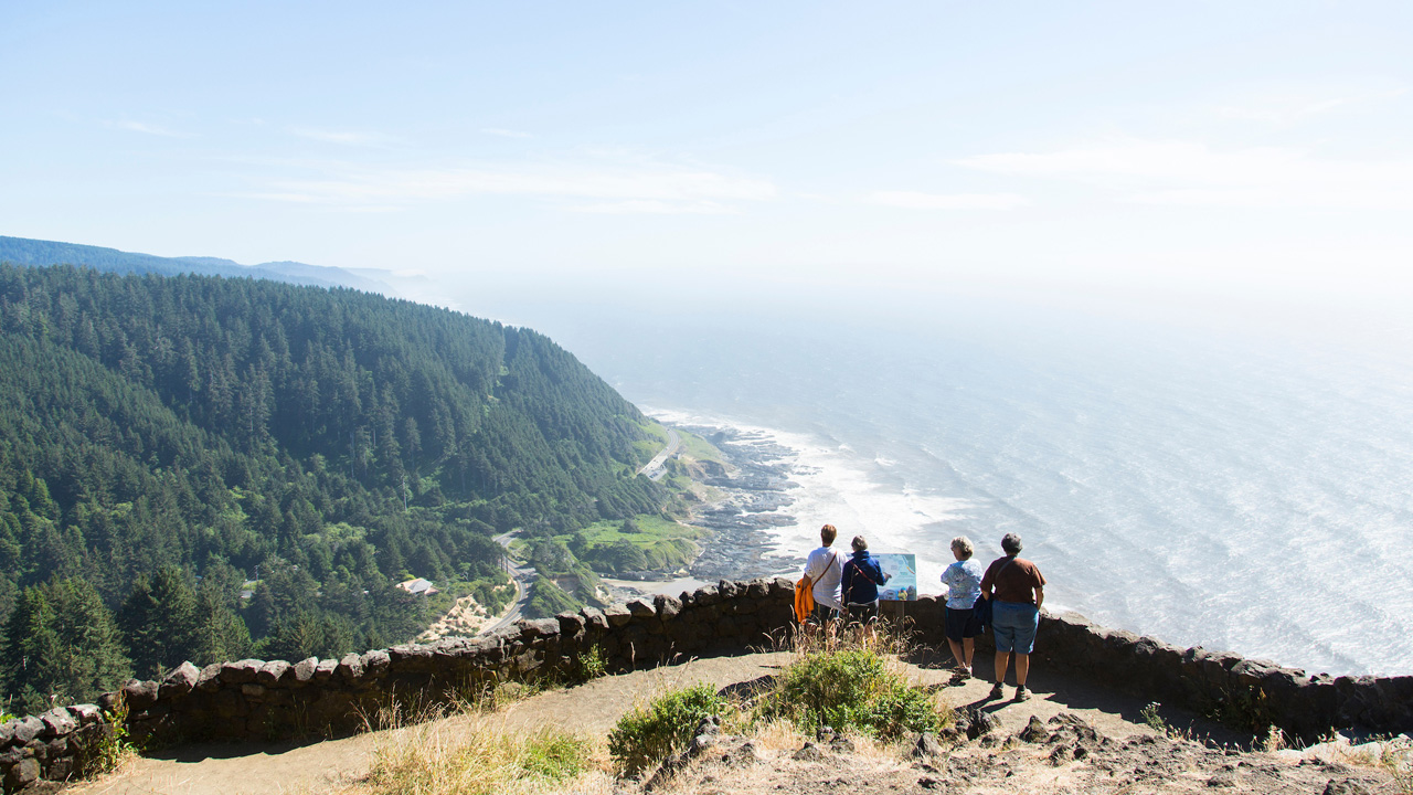 People stand at a high-elevation overlook with the ocean and Hwy. 101 below