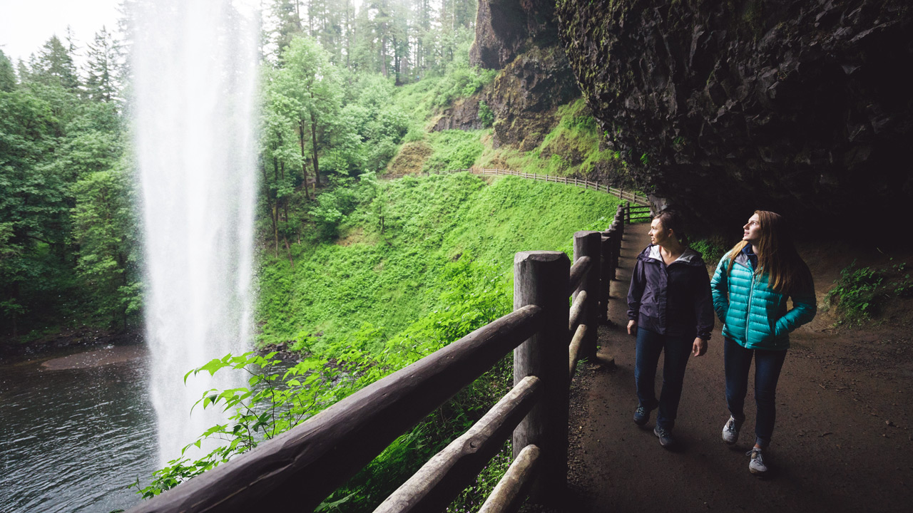 A couple walk behind a waterfall