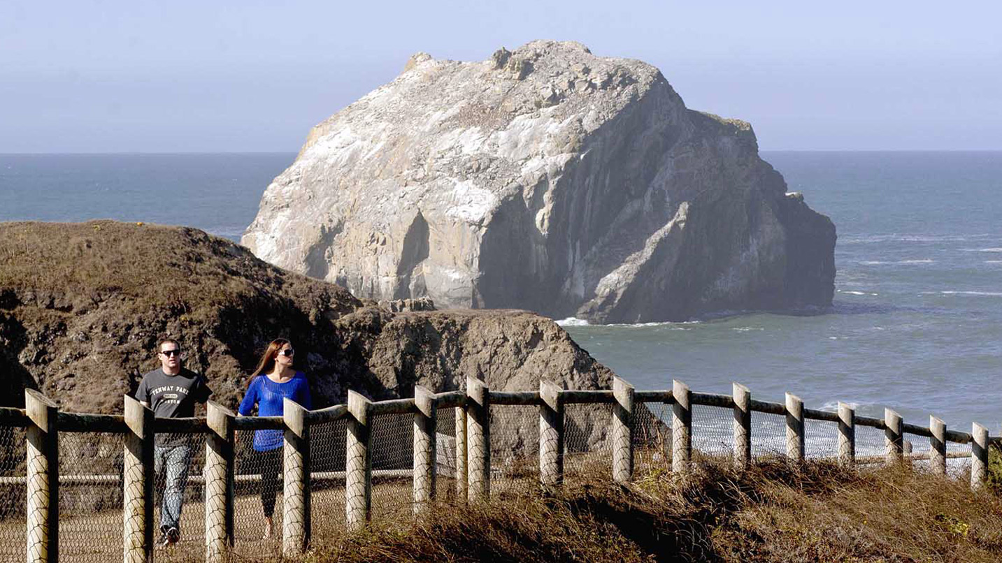 A couple walks up the path from the aptly named Face Rock.