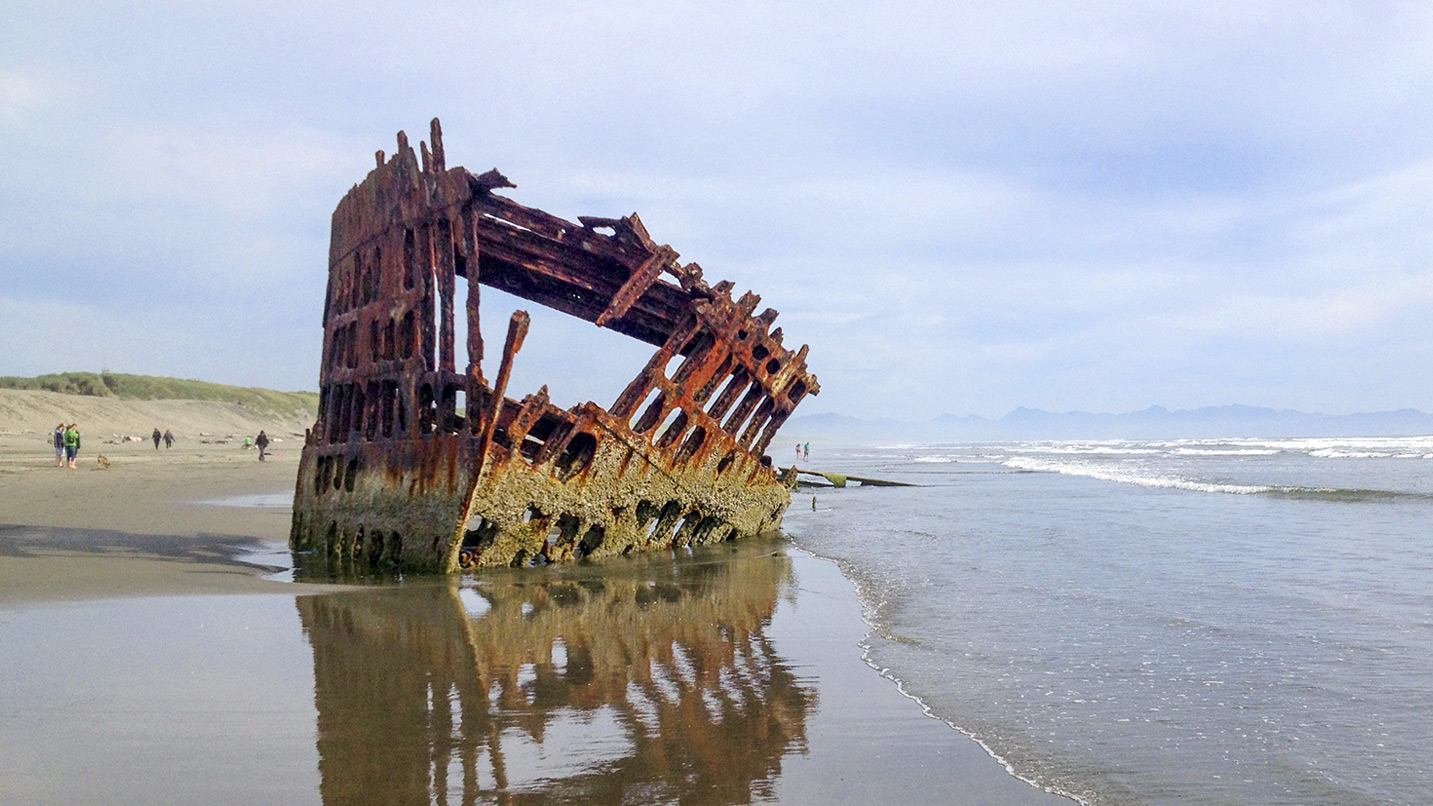 A shipwreck rusts on the shoreline.