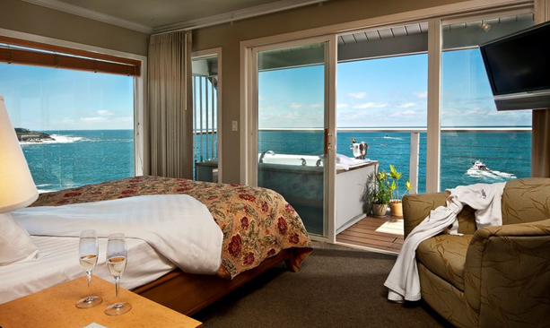 An oceanfront room boasts glass doors and a hot tub on the balcony.