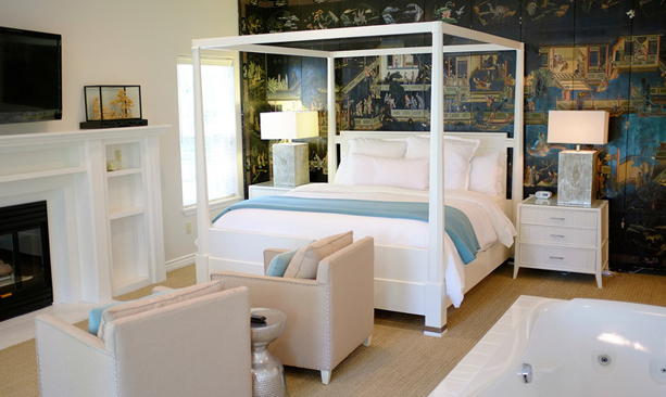 Posh white hotel room with four-post bed looks inviting.