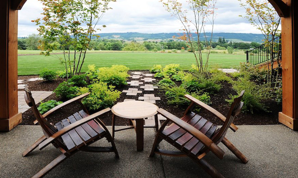 Wooden patio chairs overlook a lush field.