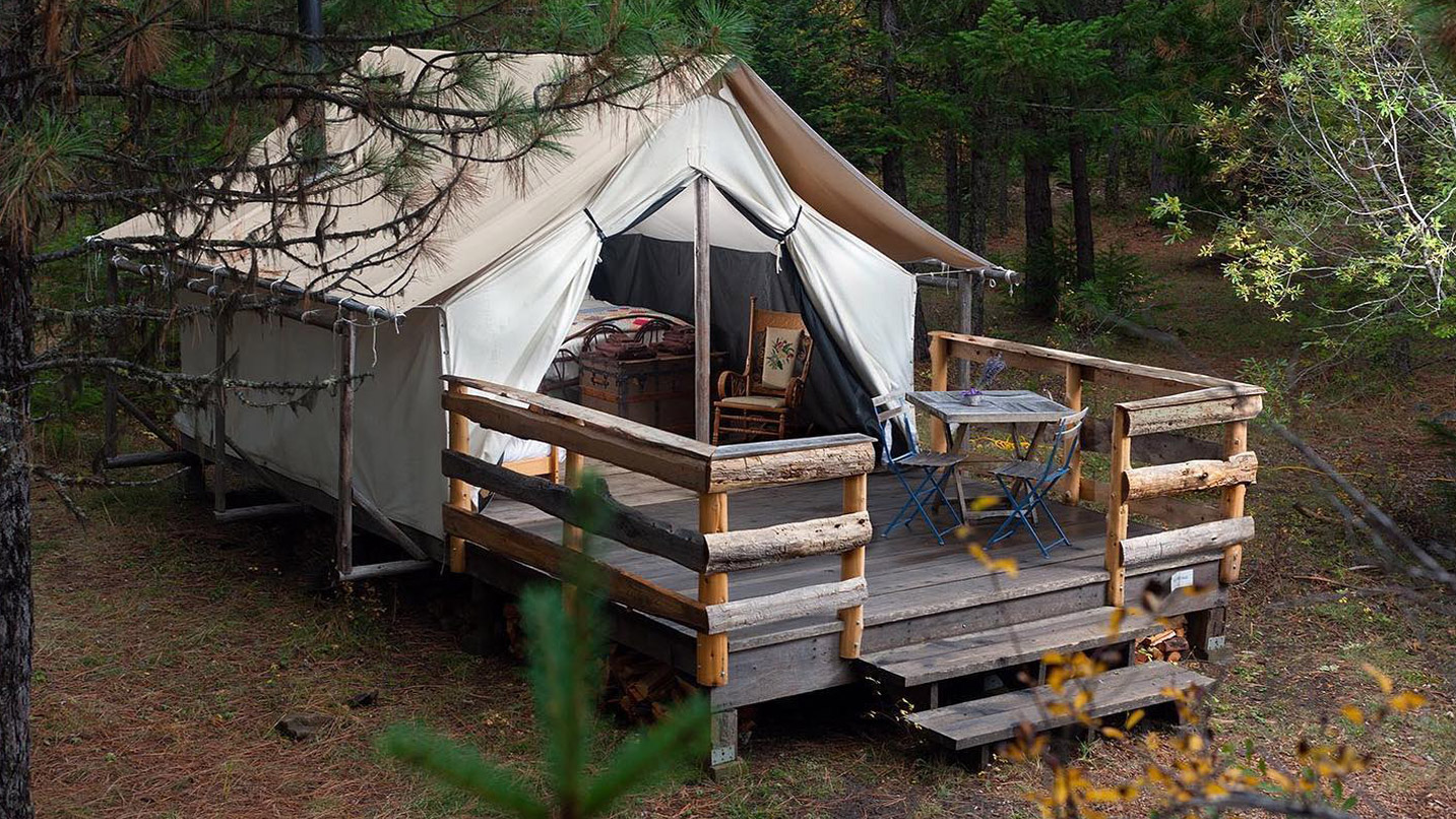 A permanent canvas tent is perched on a platform in a forest