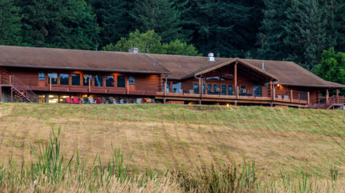 A large wooden lodge sits on top of a grassy hill