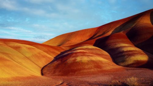 Named for the delicate layers of reds, yellows, golds and blacks in its soil, the Painted Hills is one of the three units that make up the John Day Fossil Beds National Monument. (Photo credit: Chantal Anderson)