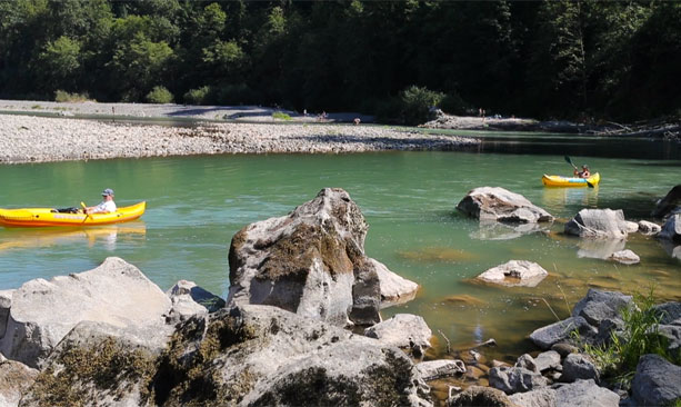 Two people in yellow kayaks paddle down the Sandy River
