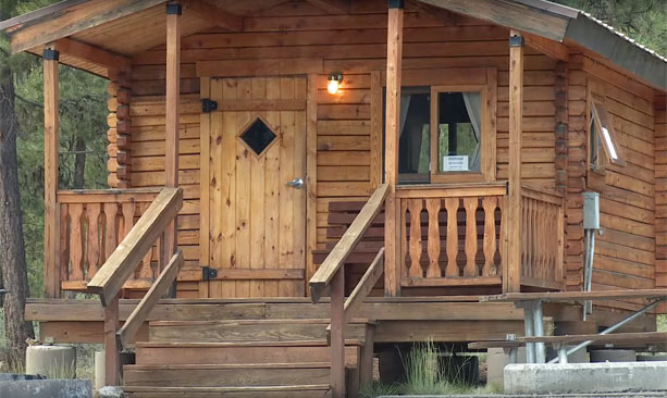 The exterior of a log cabin with a covered front porch