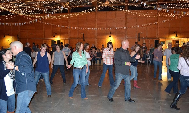 People laugh as they side step at the Oregon Garden Barn Dance.