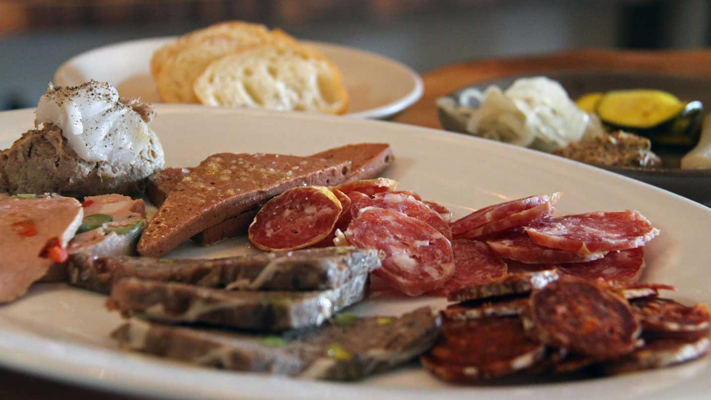 Salami and cheeses are spread across a plate.