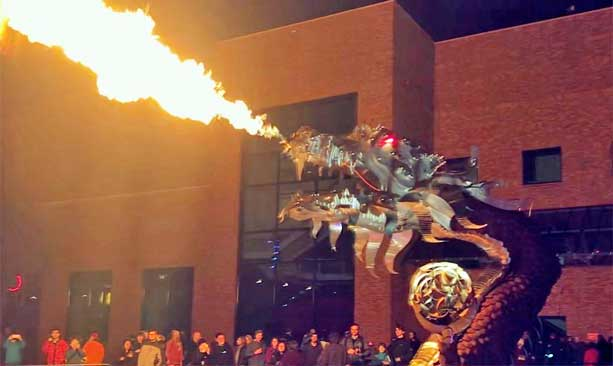 A metal dragon blows out fire in front of a wowed crowd.