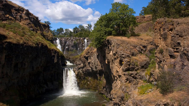 A mult-tiered waterfalls flows between rocks
