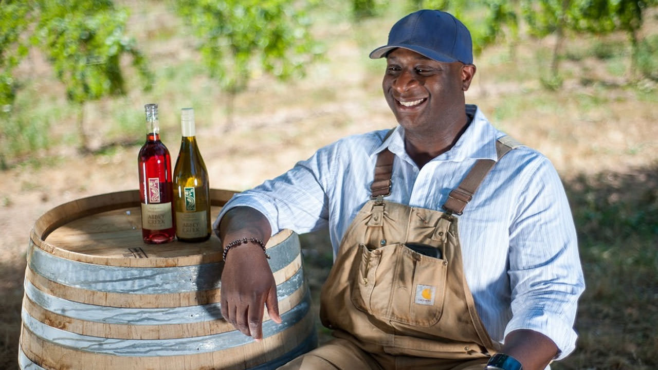 Bertony Faustin wears overalls and a collared shirt as he smiles next to two bottles of wine he made.