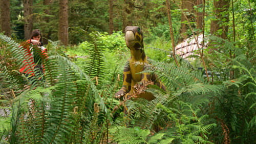 An outdoor dinosaur statue tucked into ferns