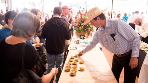 Cowboy-hat-wearing guest reaching for plate at Feast Portland
