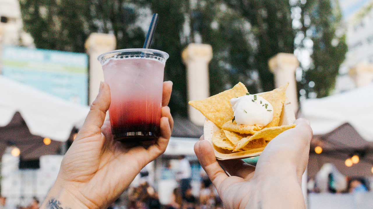 Two hands hold up a drink and chips.