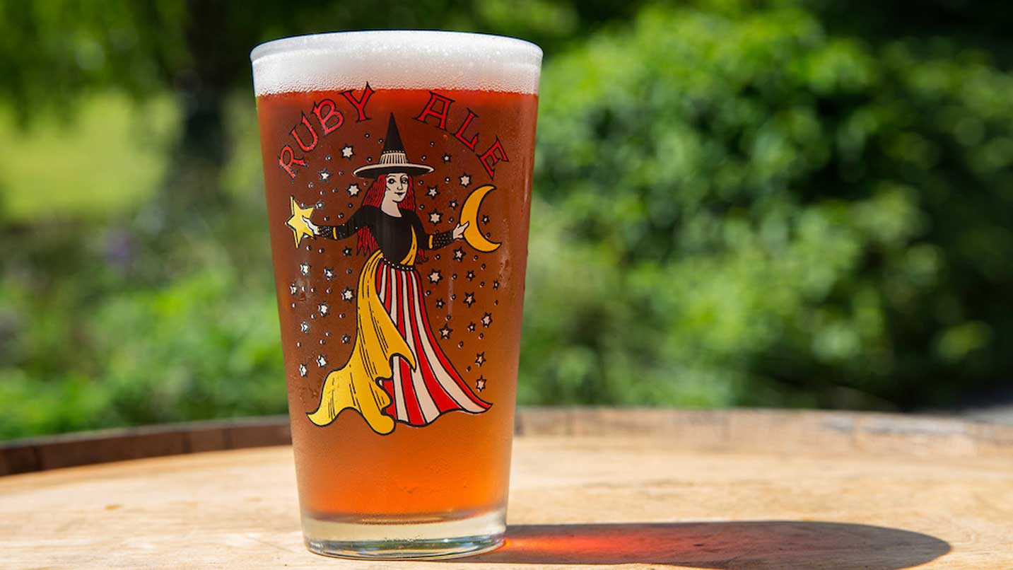A beer shines in the sun in a pint glass that bears the Ruby Ale logo.