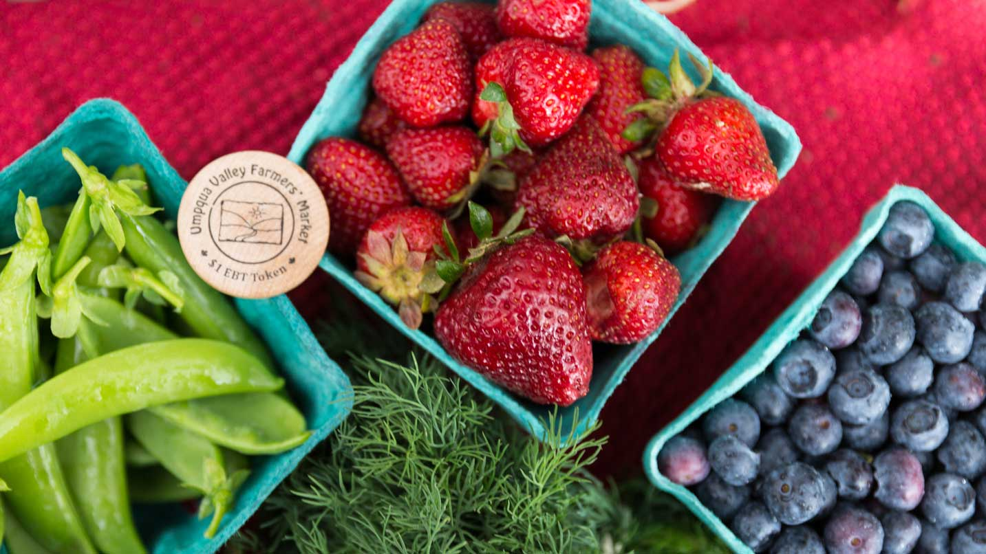 Baskets of strawberries, blueberries and snappeas.