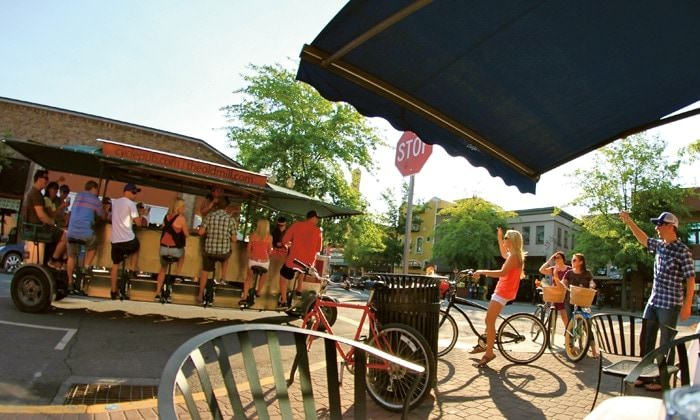 Pedestrians wave as the Cyclepub passes by in downtown Bend, Oregon