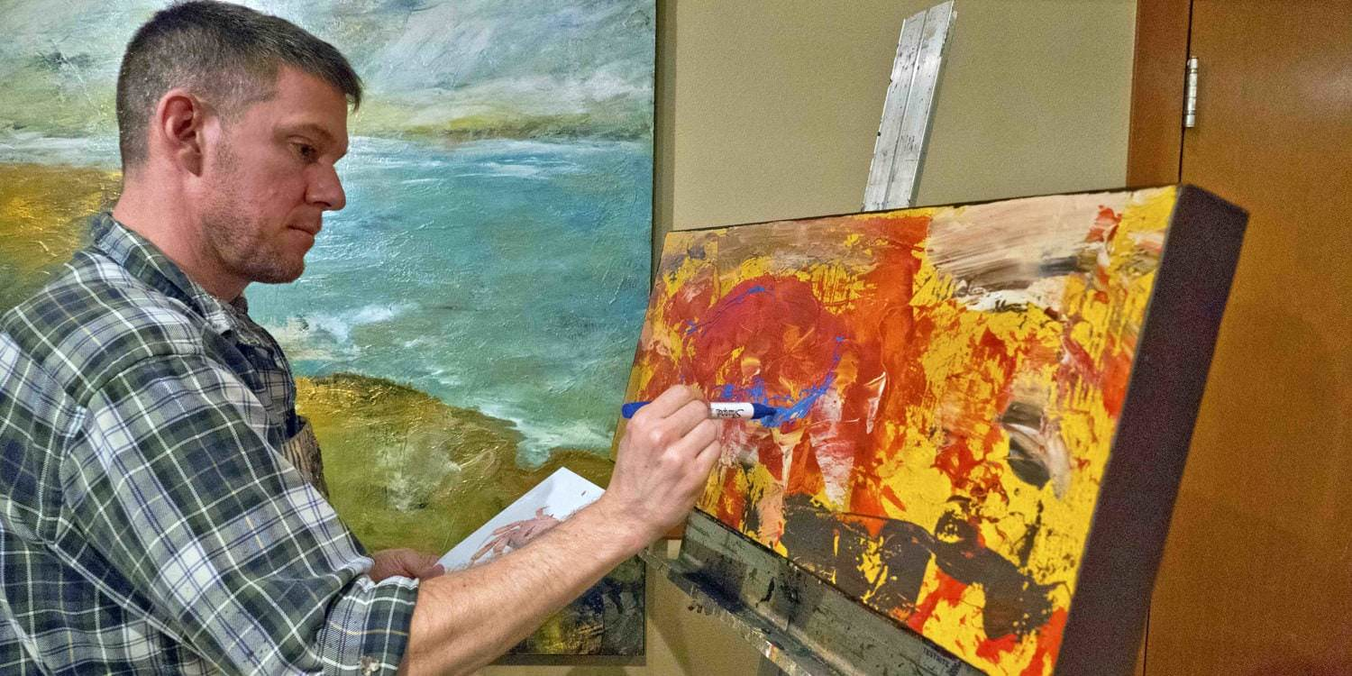 Artist Christopher Mathie works on a painting at the Arts in Action event.