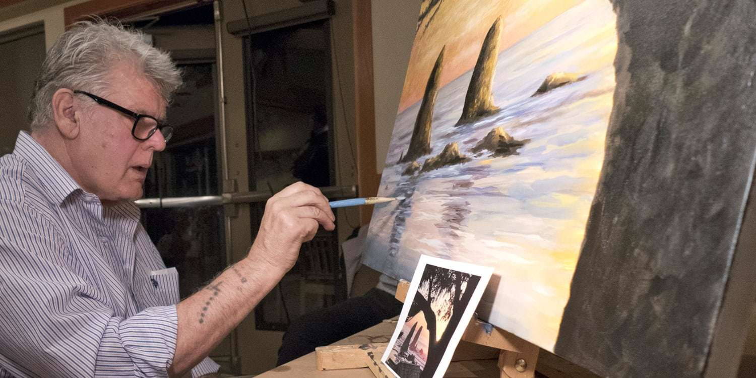 Artist and Cannon Beach gallery owner Blue Bond works on a painting at at the Arts in Action event.