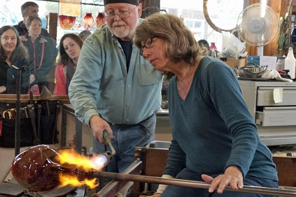 Glassblowing artist Suzanne Kindland, assisted by Jim Kingwell, works on a piece during Stormy Weather Arts Festival.