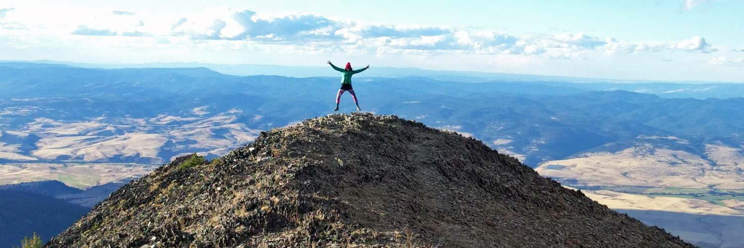 Woman with arms spread open at the top of mountain