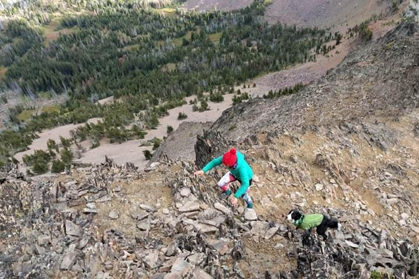 Woman using hands to scramble up rocky mountain