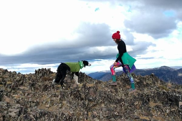 Woman and dog walking on more level part of mountaintop