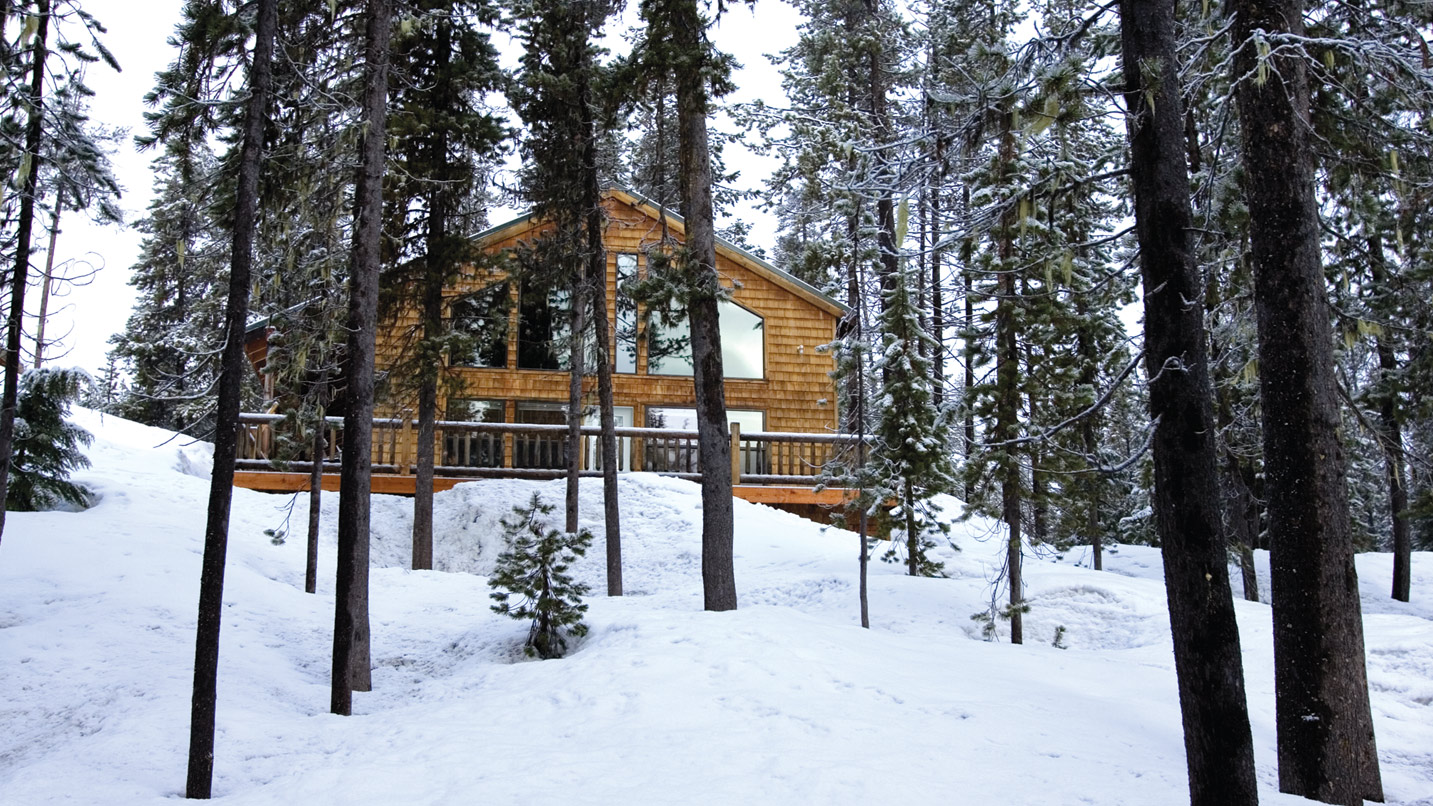 A two-story A-frame cabin sits in a snowy forest