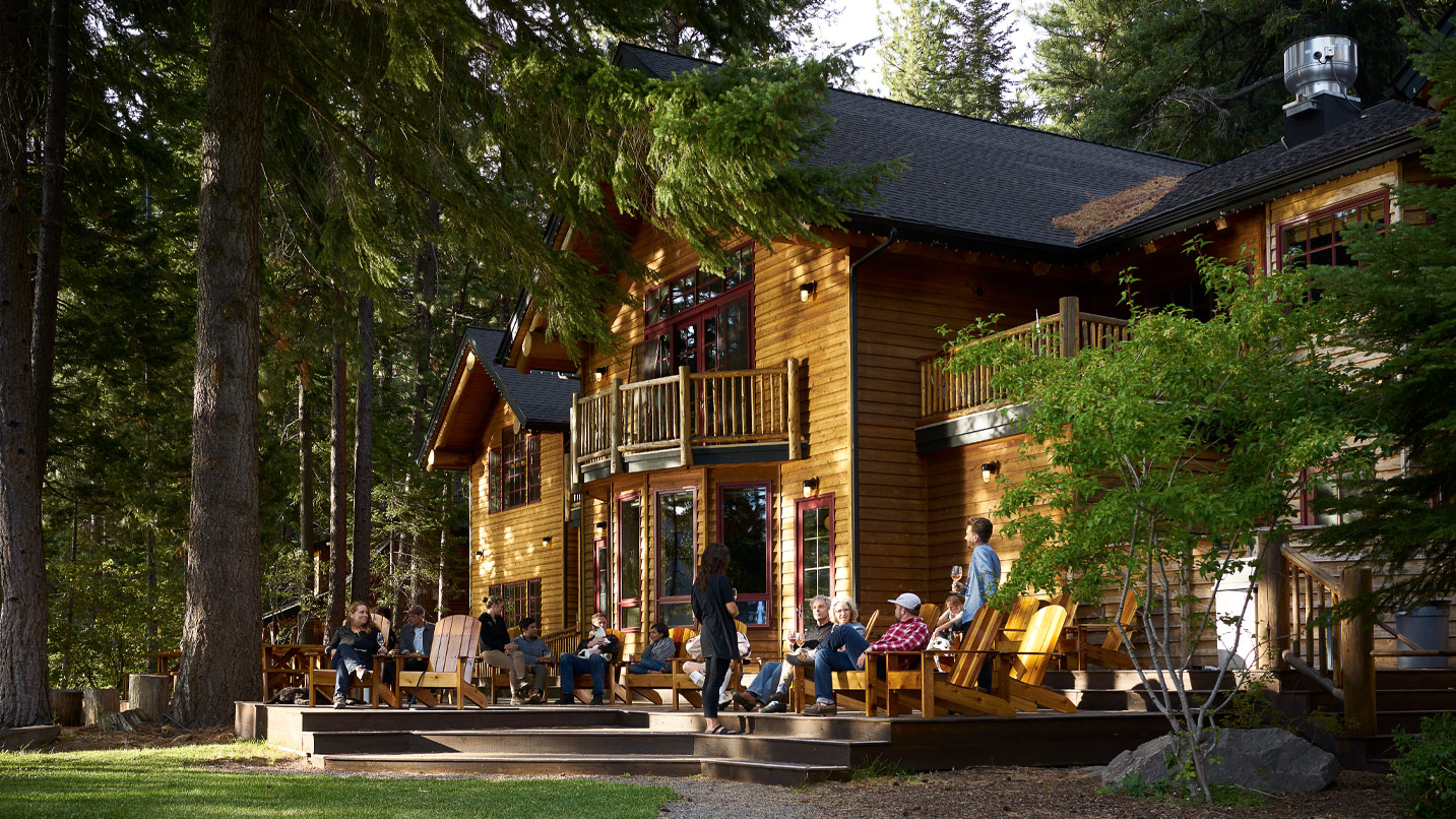 People sit on a wooden deck in front of a two story lodge