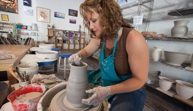Woman forming clay into a tall vase