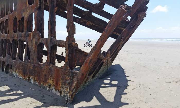 A rusty shipwreck sits on a sandy beach, with a bicyclist in the background.