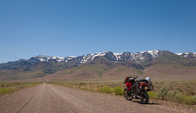 Motorcycle pulled off to the side of the road in front of the snow-capped Steens Mountain