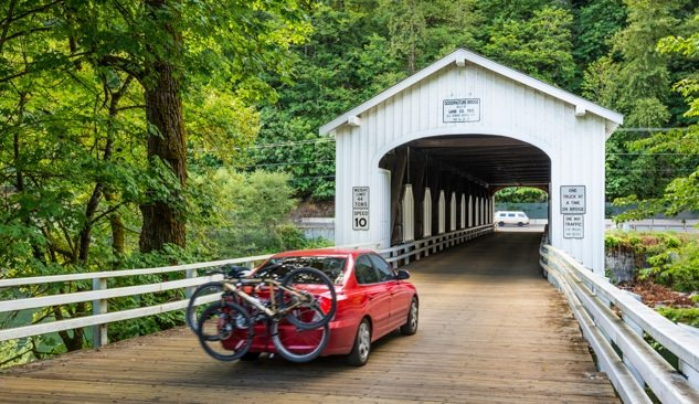 Red car carrying two bikes on Goodpasture Bridge