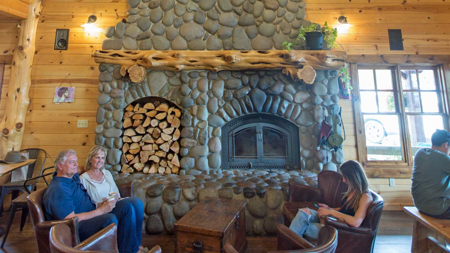 A couple sips coffee in front of a large stone fireplace.