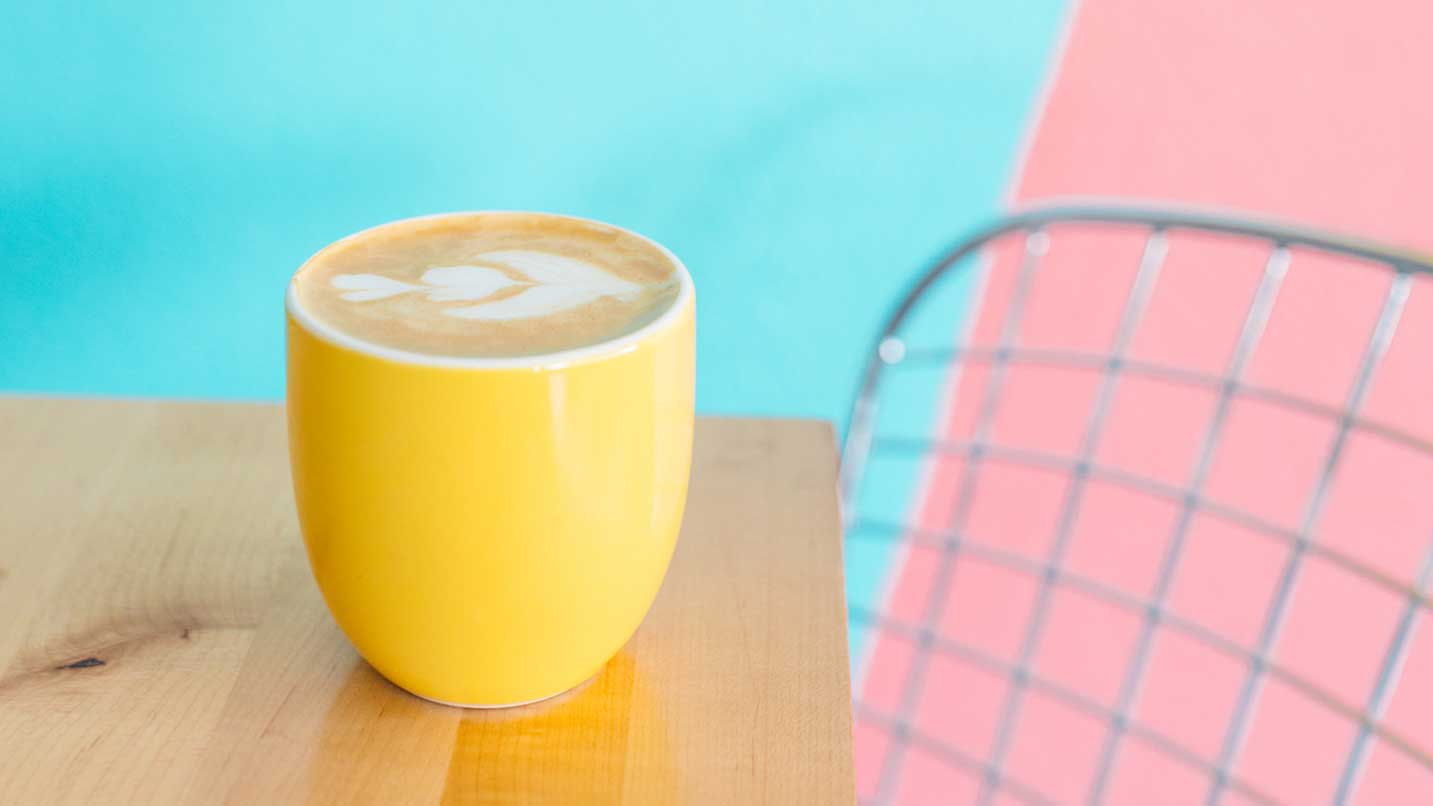 A latte in a yellow mug sits on a wooden table in front of a pink and blue painted wall.