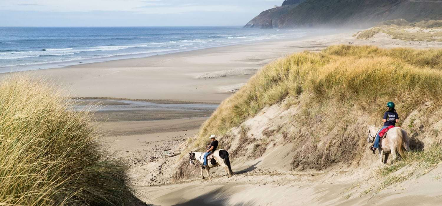 Two people on horseback journey down sand dunes to the coastline.