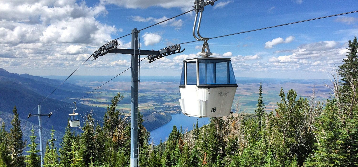 A tramway overlooks tree tops and the brilliant blue Wallowa Lake.