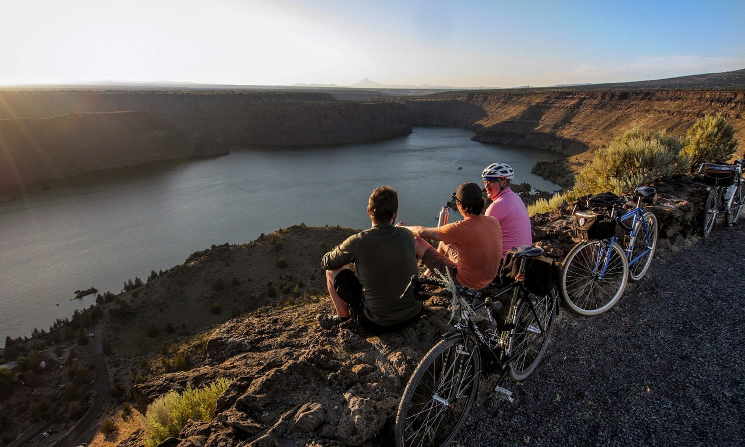 Bicyclists take a break at a rocky overlook above Lake Billy Chinook on the Madras Mountain Views Scenic Bikeway