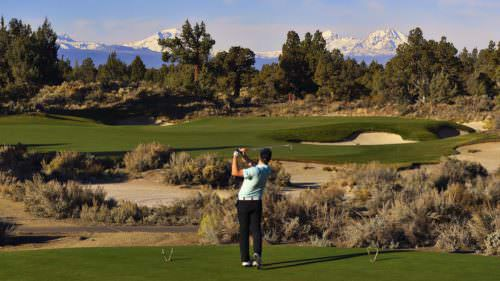 Golfer swinging at Central Oregon course