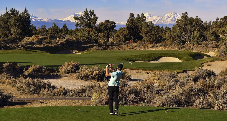 Golfer swinging at Central Oregon course