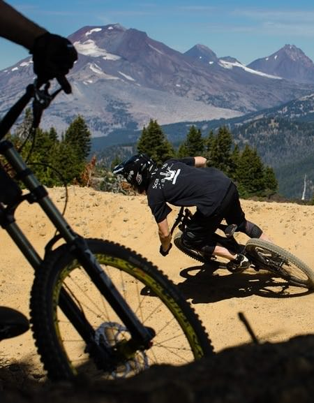 A mountain biker making a sharp descent with mountains in the distance