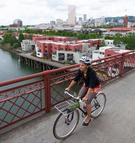 Cycling commuter on a bridge with city buildings in the background