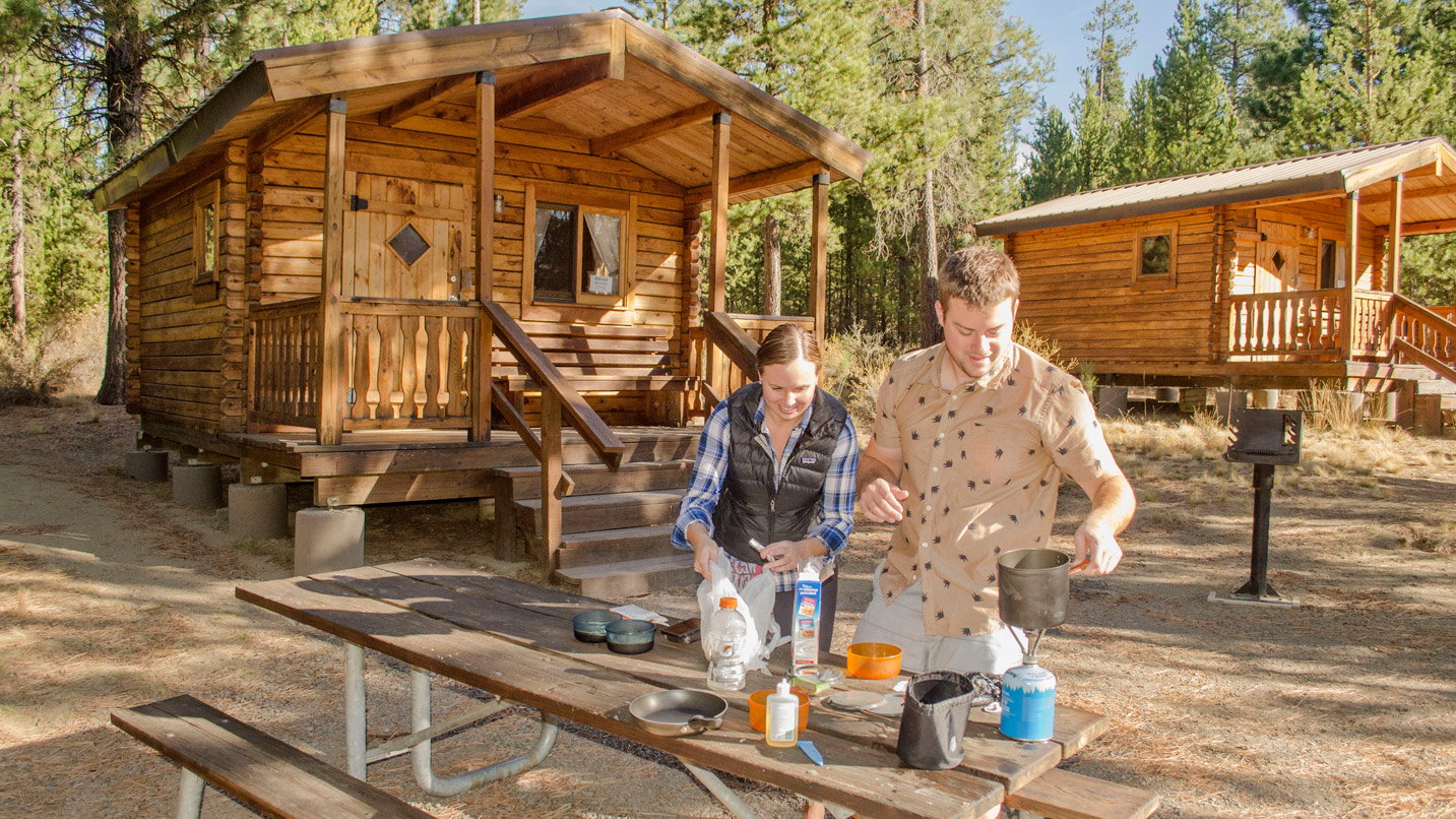 Two people cook on a picnic table in front of a cabin