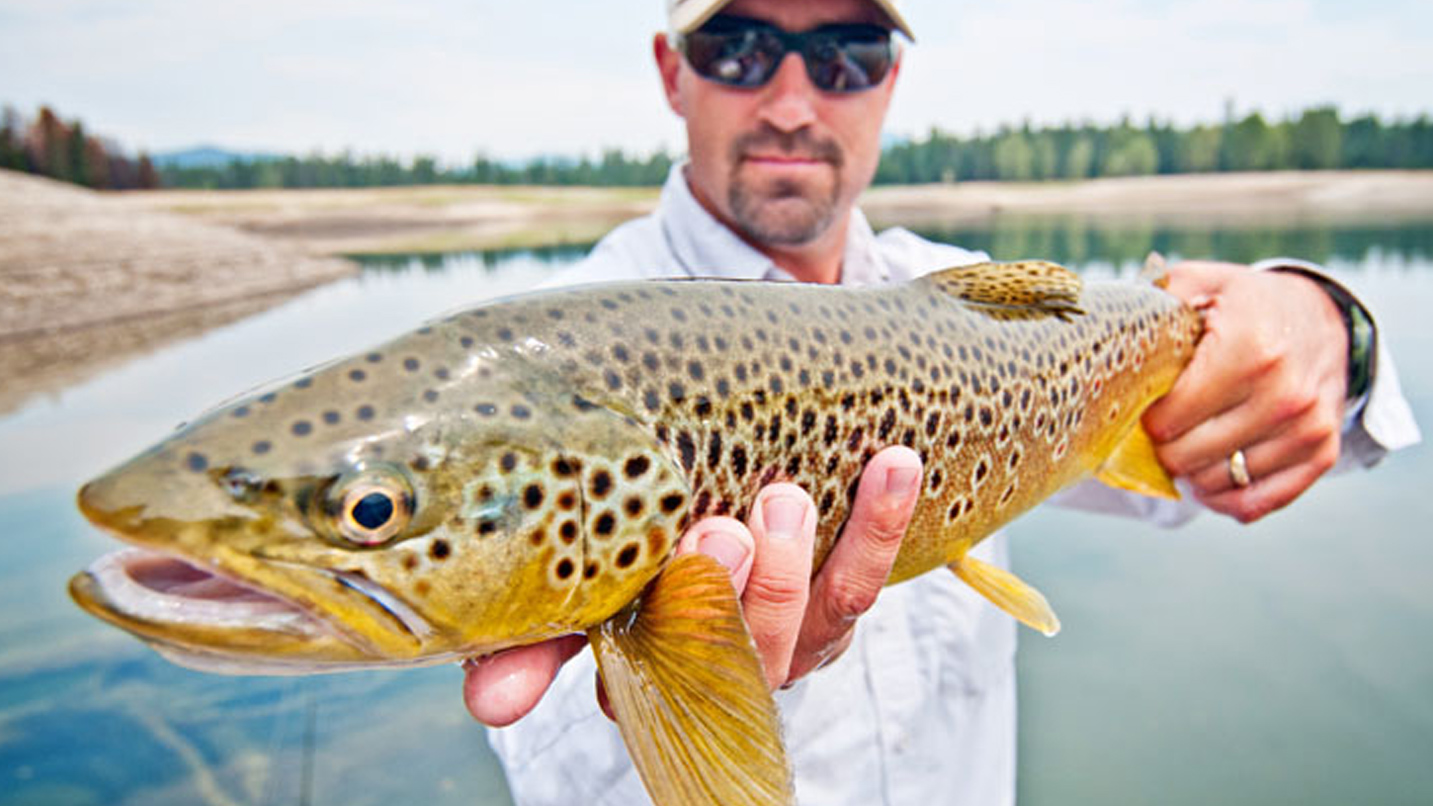 A man holds a large fish up to the camera